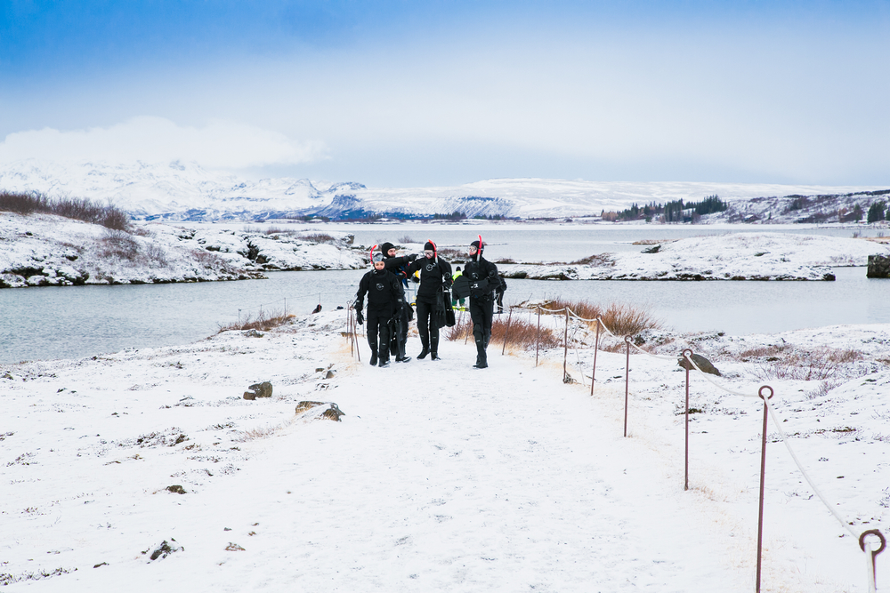A group of dpeople walk back to their destination after their silfra snorkeling tour. There is snow on the ground around them.