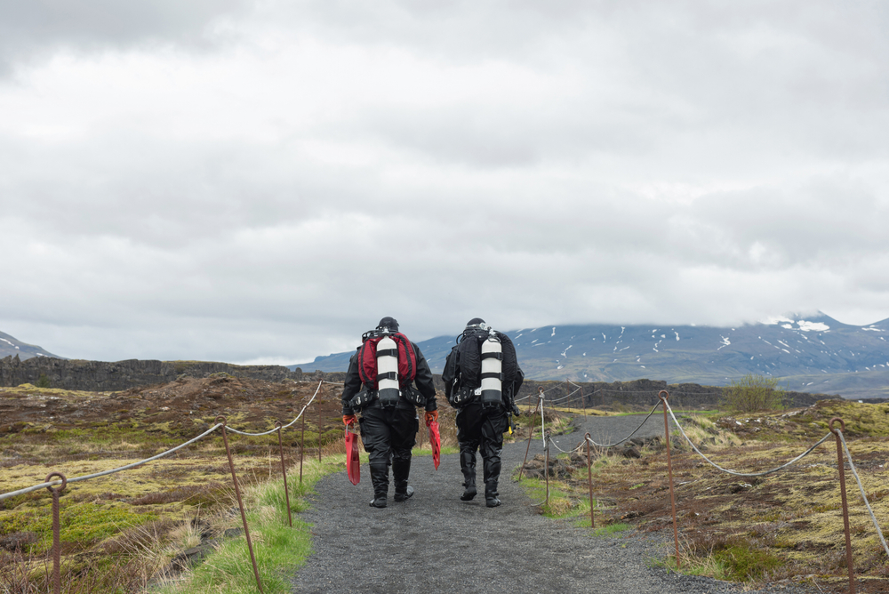 Two divers walk on a path toward the Silfra fissure in iceland