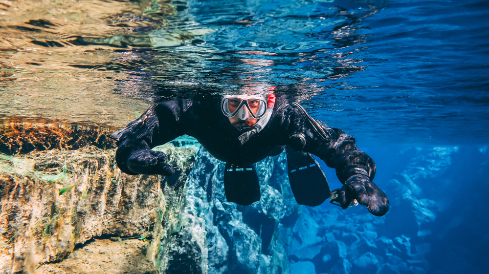 Man in a snorkel mask swims toward camera in the blue waters of the Silfra fissure