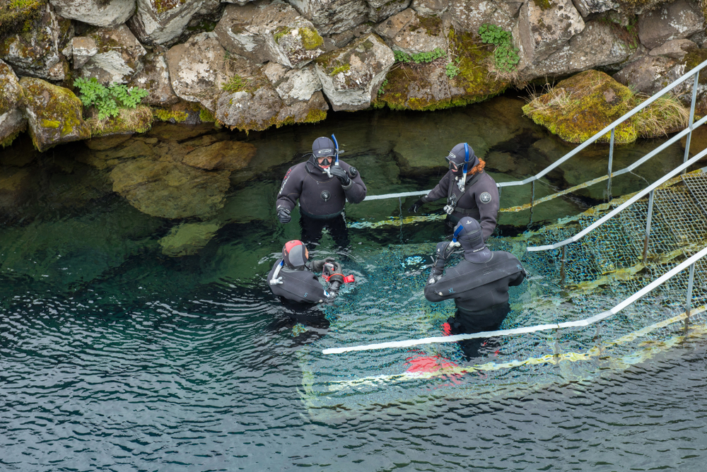 A group of divers gather at the launch pad of the fissure, ready to begin their silfra snorkeling tour