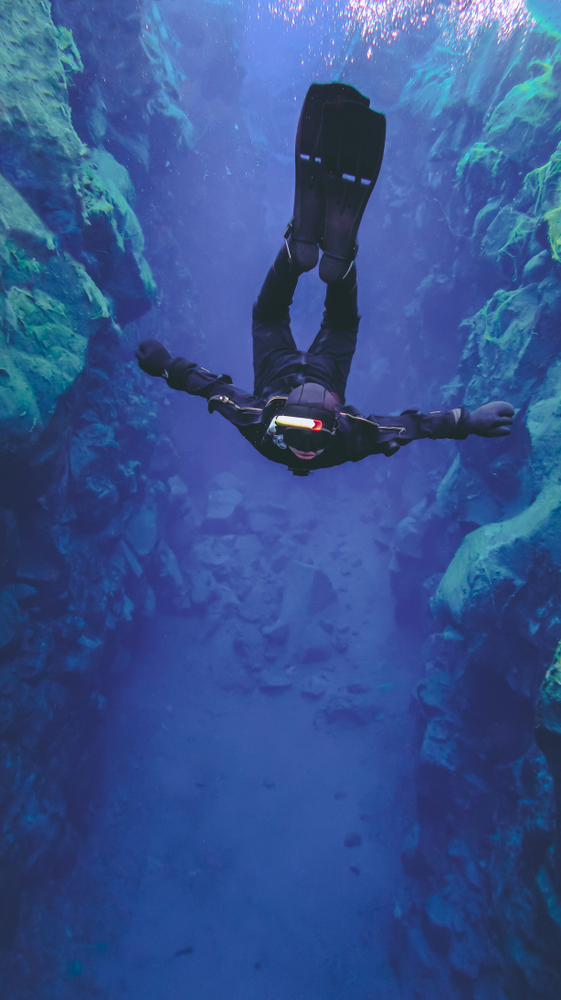 person silfra snorkeling in iceland does a backflip and floats through the blue waters, almost as if weightless.