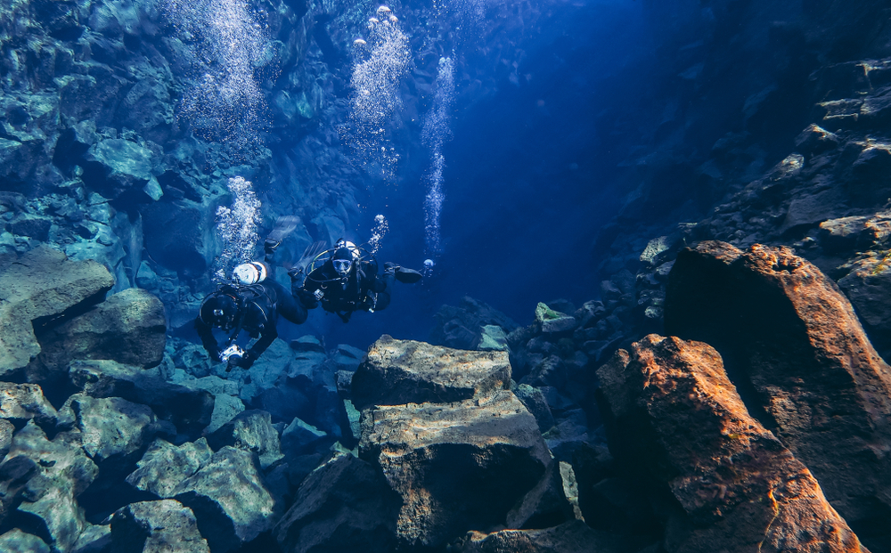 Two divers in iceland silfra fissure are deep in the fissure, their bubbles rising to the surface.