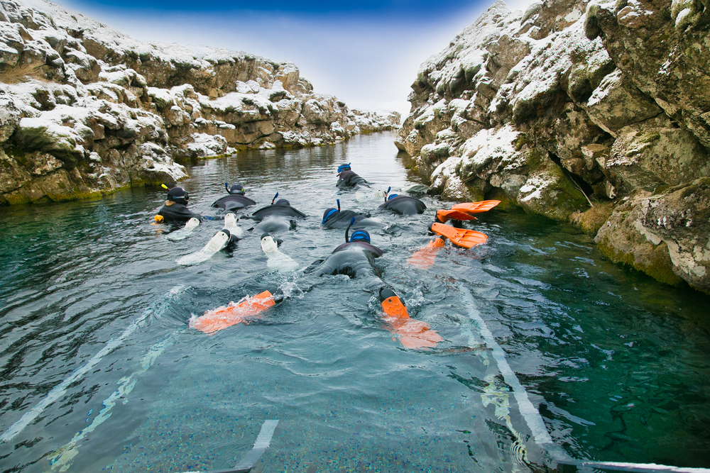 Silfra fissure Snorkelers with orange fins float through a fissure.